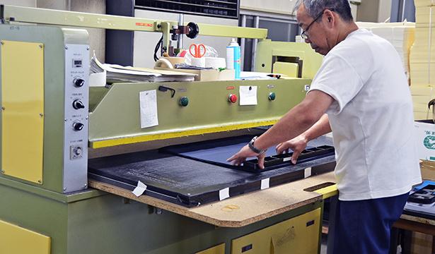 男性が機械に向かって作業