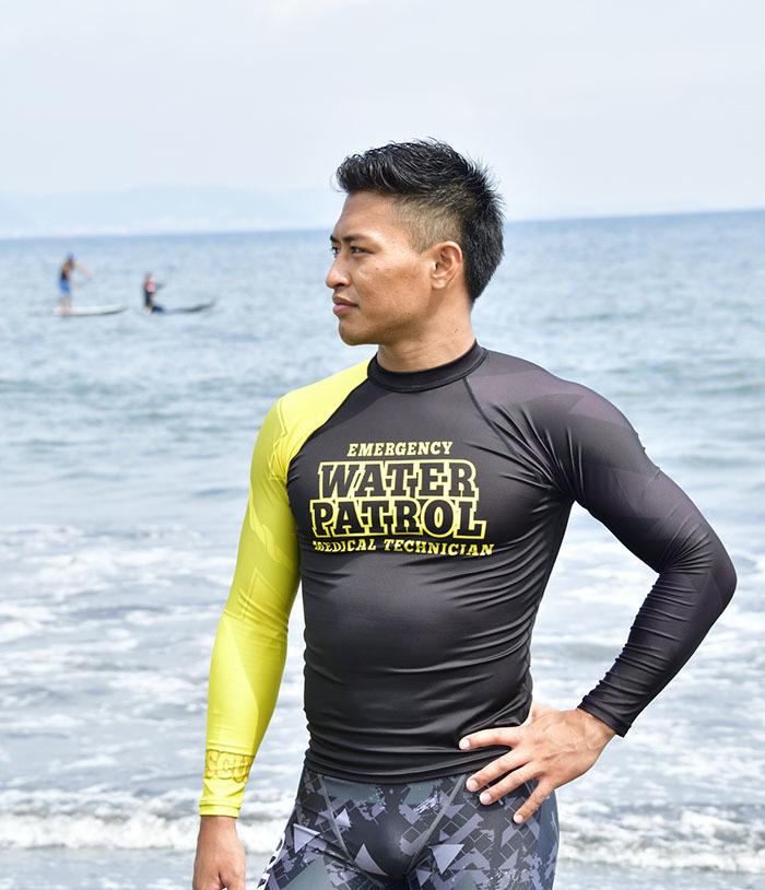 超撥水ラッシュガードを着用した男性が海岸に立っている