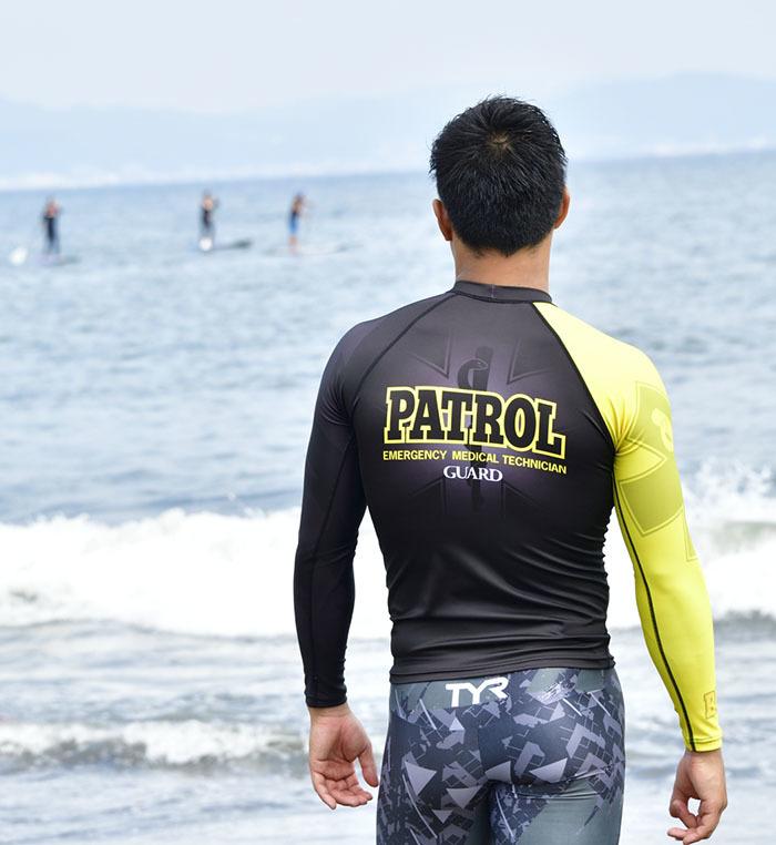 超撥水ラッシュガードを着用した男性が海岸で海を眺めている